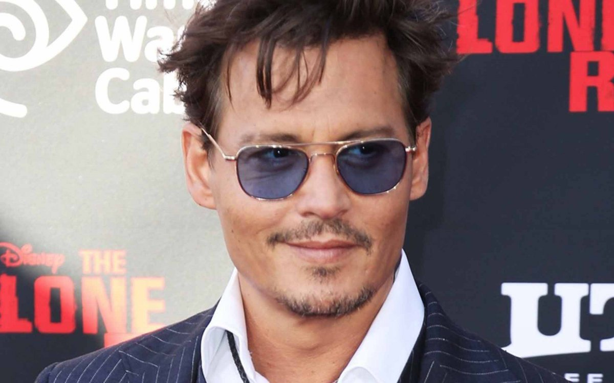 Johnny Depp showing off blue sunglass lenses while promoting The Lone Ranger!